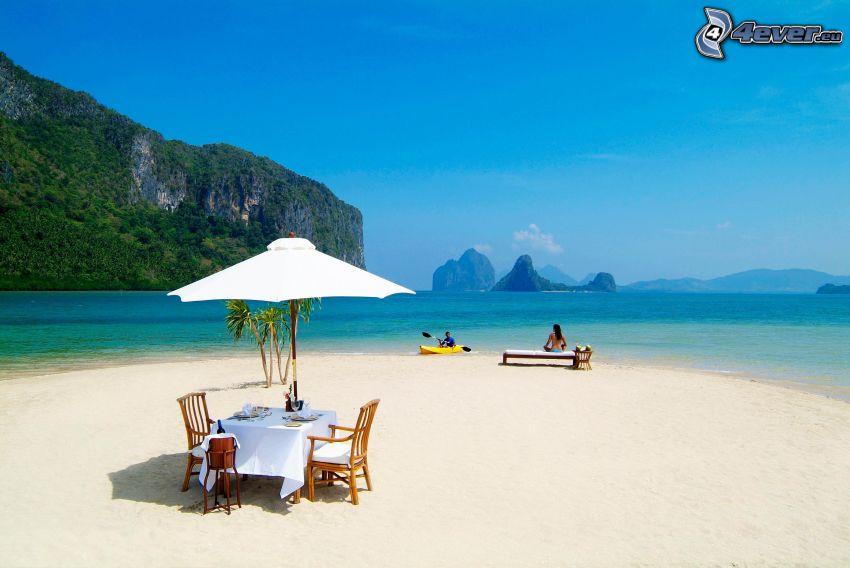 seduta, spiaggia sabbiosa, mare azzurro, rocce nel mare
