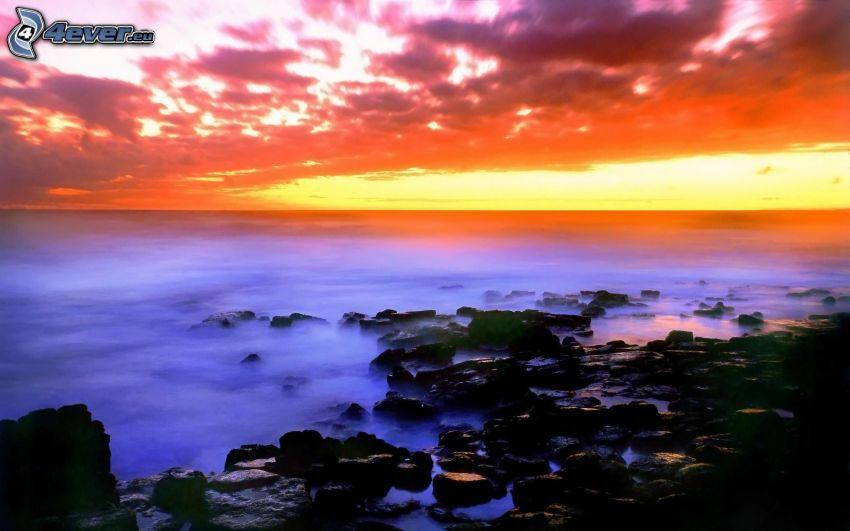 Spiaggia al tramonto, costa rocciosa, mare, cielo arancione