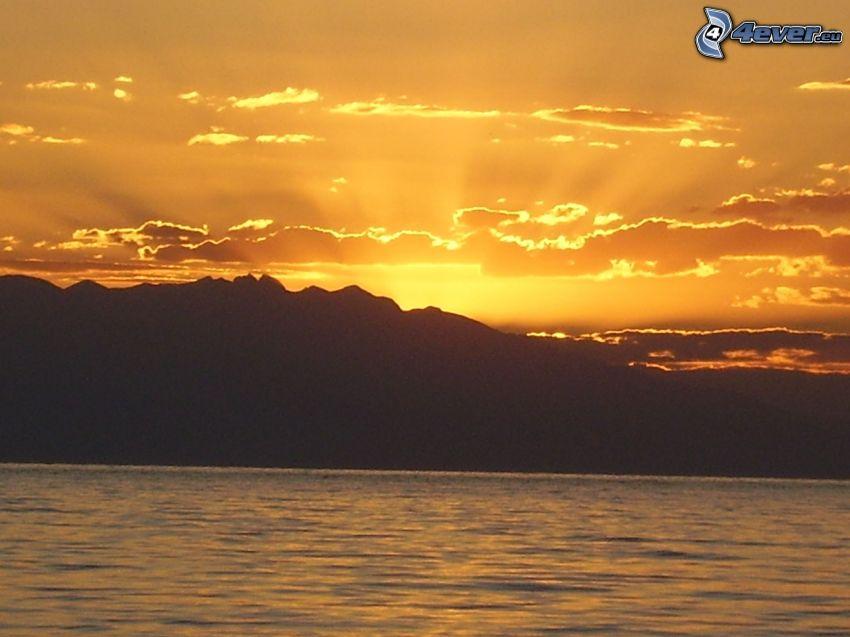 tramonto dietro le montagne, cielo arancione, raggi del sole, lago grande