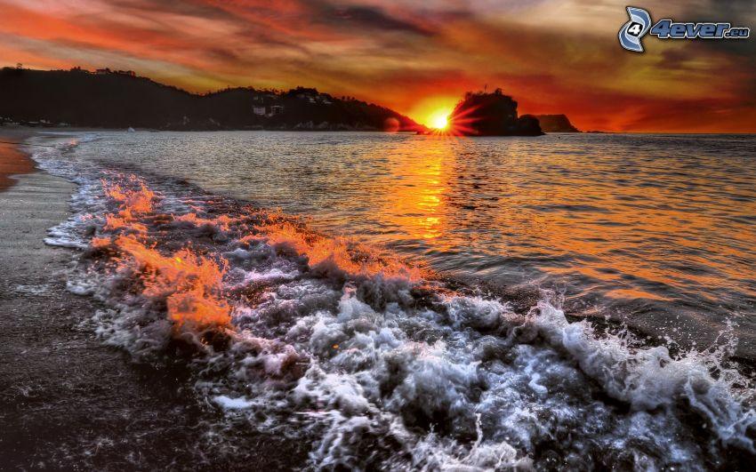 Tramonto sul mare, onde sulla costa