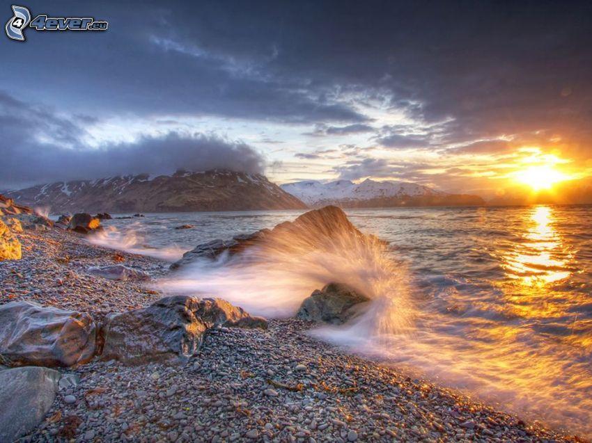 Tramonto sul mare, spiaggia di rocce, onde sulla costa, montagne