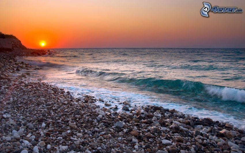 tramonto sulla spiaggia scogliosa, onde sulla costa, mare