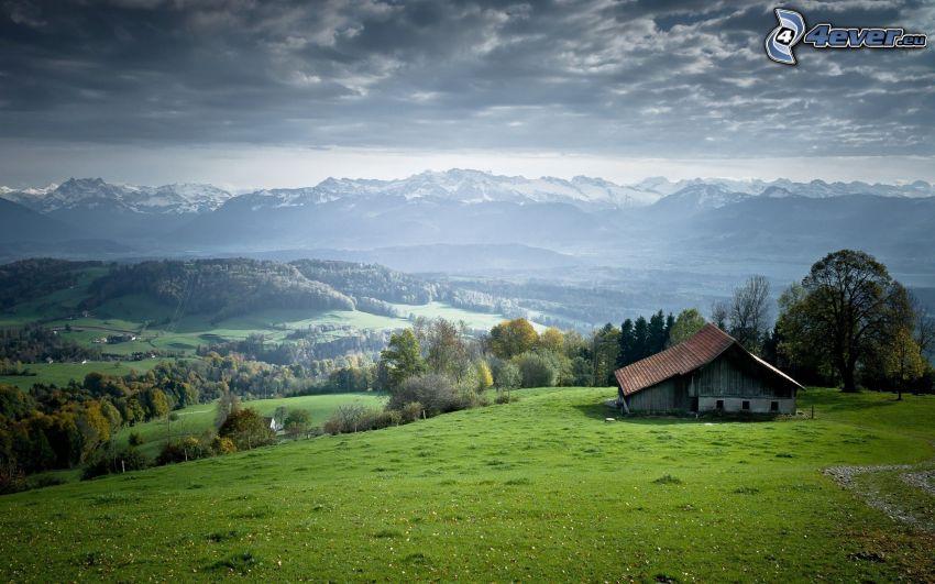 casa, montagne, boschi e prati, nuvole scure