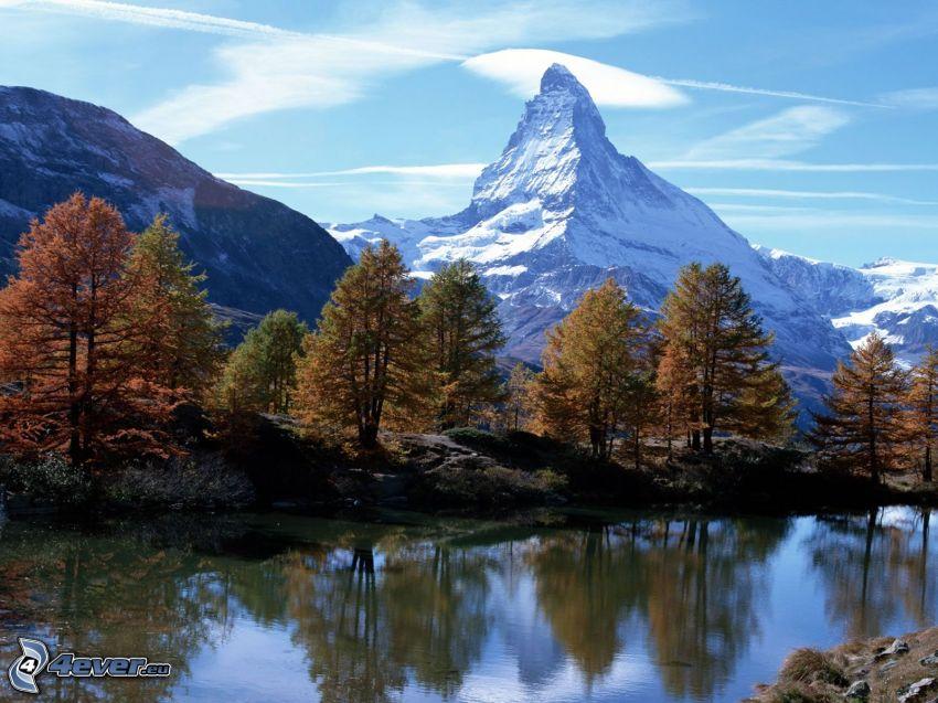 Cervino, Svizzera, alberi di autunno in riva al fiume, montagne