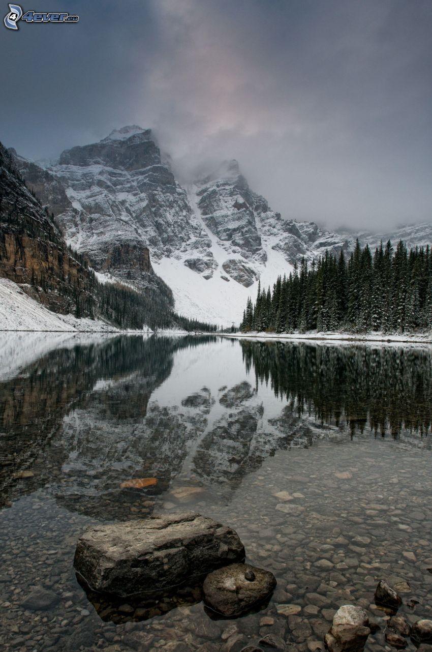 montagne innevate, montagne nelle nuvole, lago, bosco di conifere