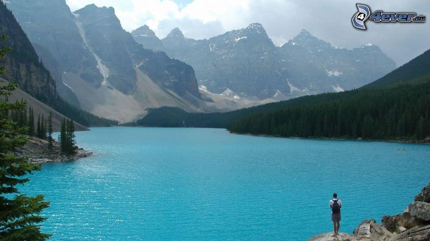 Moraine Lake, lago azzurro, montagne alte, bosco di conifere, turista