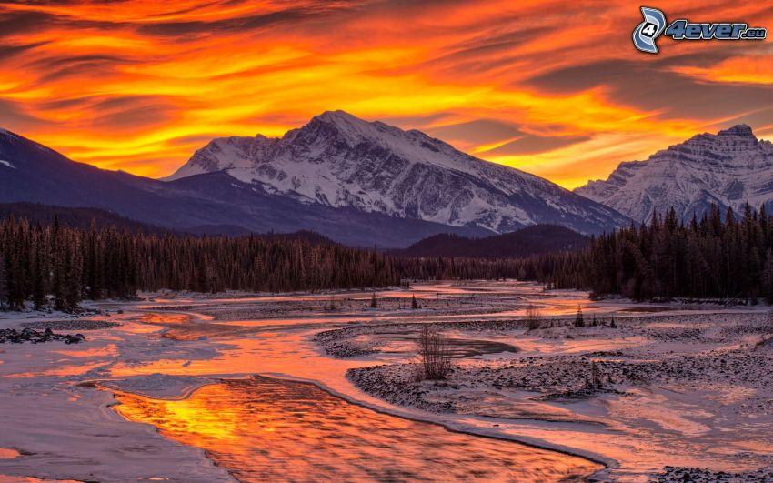 ruscello, montagne innevate, bosco di conifere, tramonto arancio