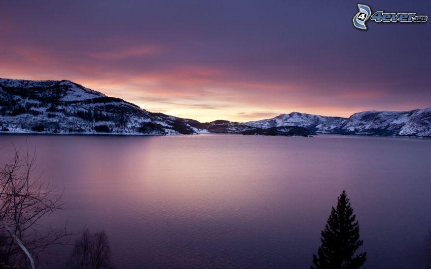 lago, colline coperte di neve, dopo il tramonto