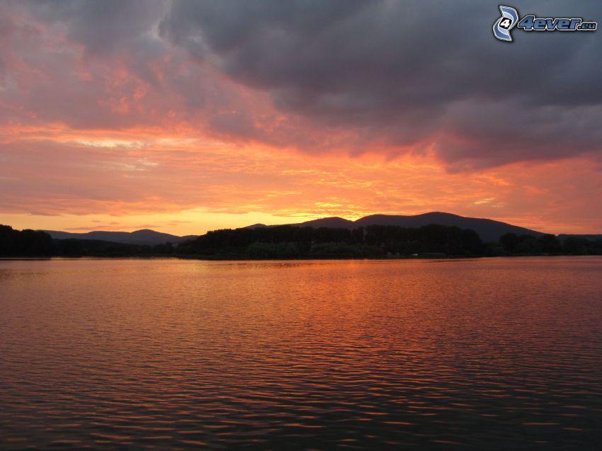serata all'alba, cielo arancione, acqua, nuvole