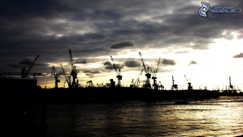 tramonto nel porto, gru, siluette, nuvole