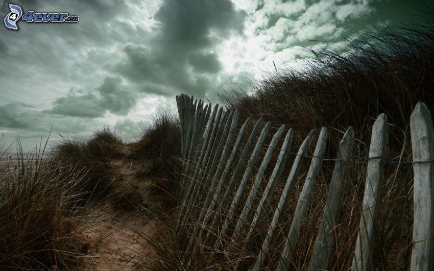 vecchio recinto di legno, erba alta, nuvole