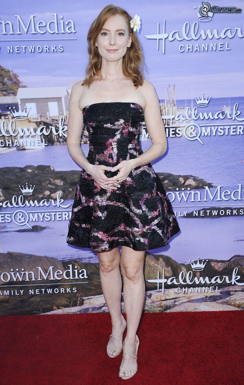 Alicia Witt, mini vestito nero, fiore nei capelli