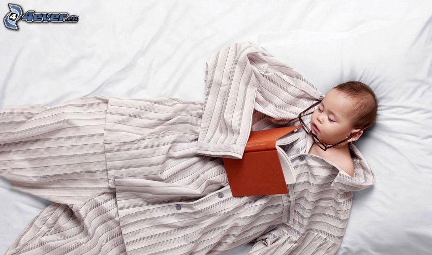 bambino che dorme, pigiama, libro, occhiali