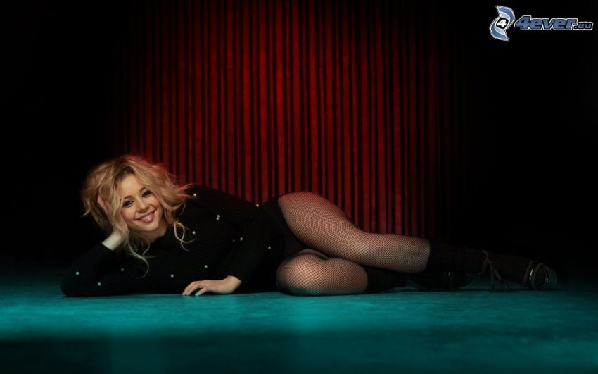 Tina Karol, sorriso, sexy gambe in calze reticolati