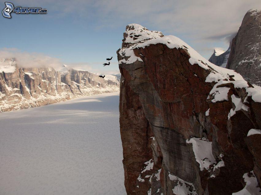 BASE Jump, scogliera, roccia, fiume nell'inverno