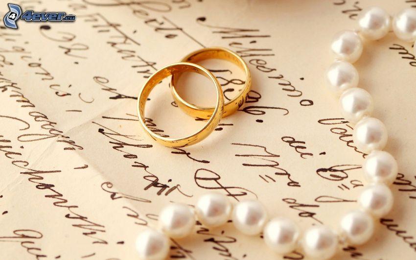 anelli di nozze, collana di perle, text
