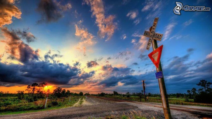 vasúti átjáró, útjelző tábla, naplemente a réten, sötét felhők, HDR