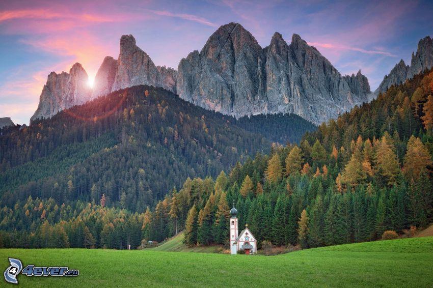 Val di Funes, templom, tűlevelű erdő, sziklás hegységek, naplemente a hegyek mögött, Olaszország