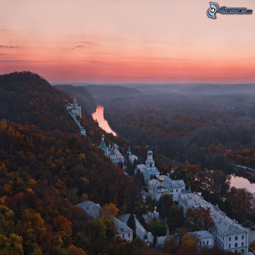 kilátás a városra, rózsaszín ég, színes fák, domb
