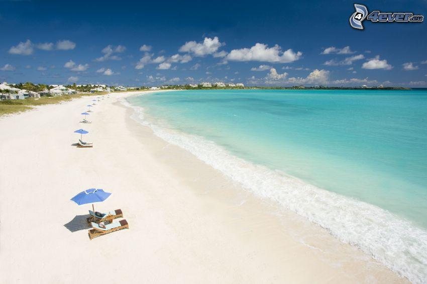 homokos tengerpart, nyugágyak, napernyők, azúrkék tenger