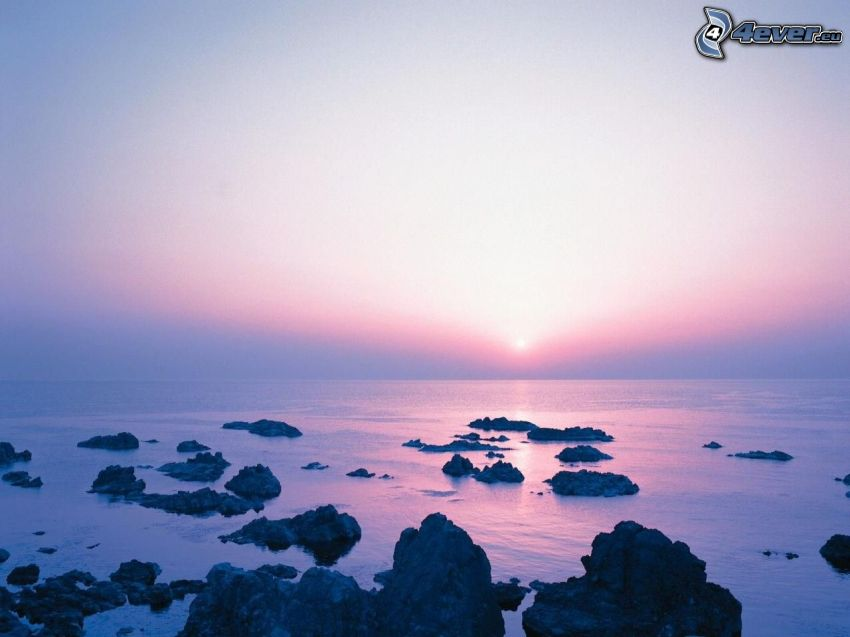 naplemente a tenger fölött, lila égbolt, óceán, sziklák, tengerpart