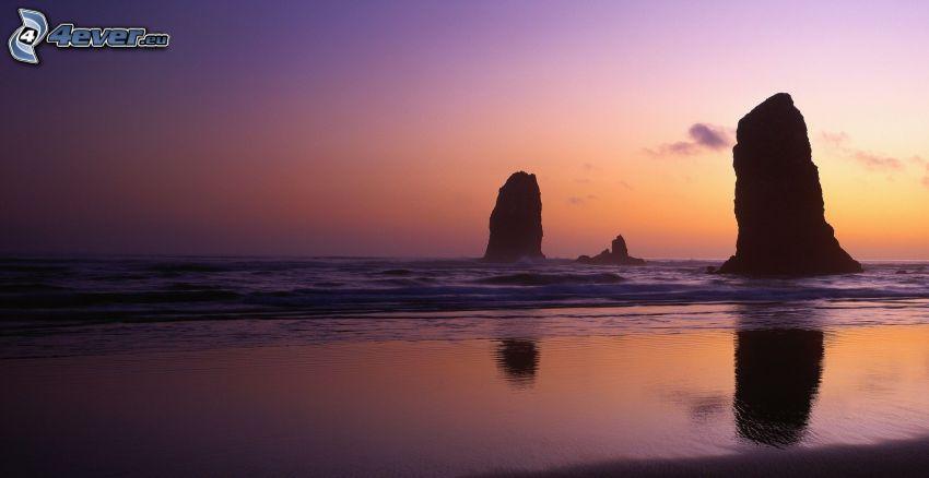 sziklák a tengerben, napnyugta után