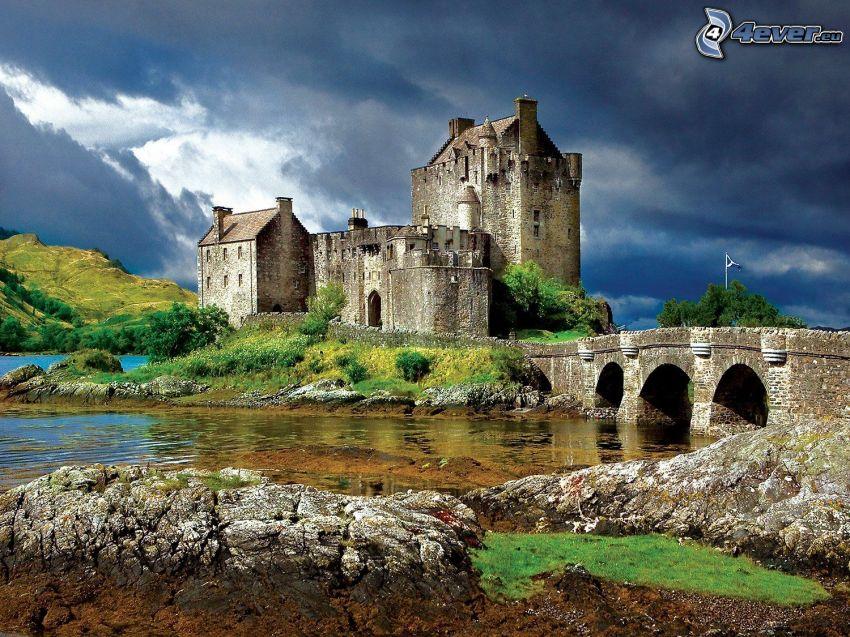 Eilean Donan, kamienny most, rzeka, ciemne chmury