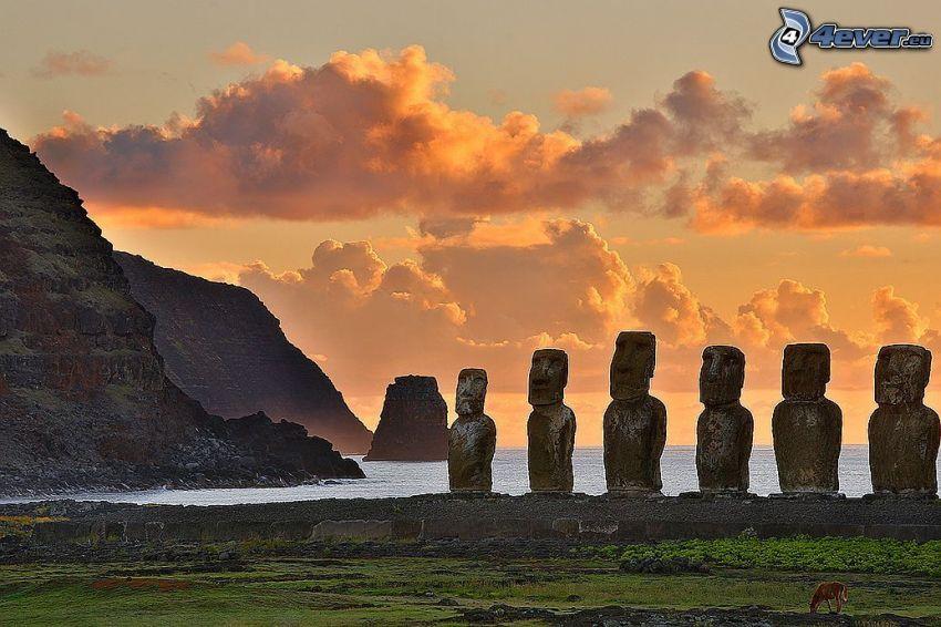 posągi Moai, nadmorskie urwiska, pomarańczowe niebo, morze, wyspy wielkanocne