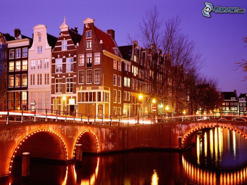 Amsterdam, kanał, domy, oświetlony most, miasto wieczorem