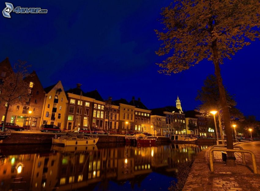 miasto nocą, uliczne oświetlenie, rzeka, łódki, domki szeregowe