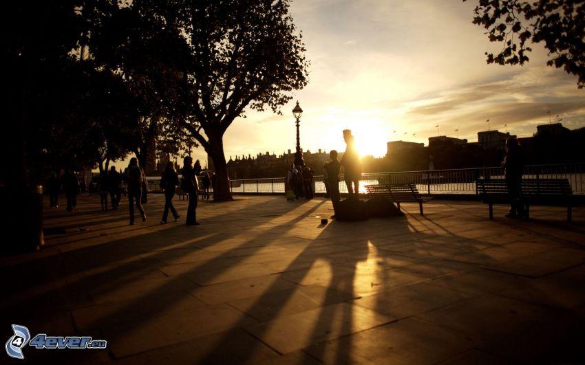 zachód słońca w mieście, ludzie, sylwetki drzew, chodnik, nabrzeże