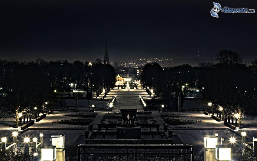 zaśnieżony park, miasto nocą