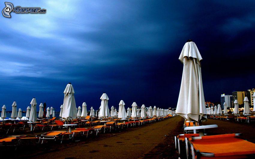 parasole przeciwsłoneczne, leżaki, ciemne niebo