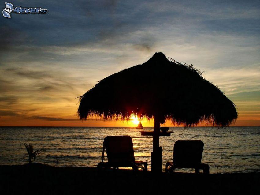 leżaki na plaży, zachód słońca nad morzem