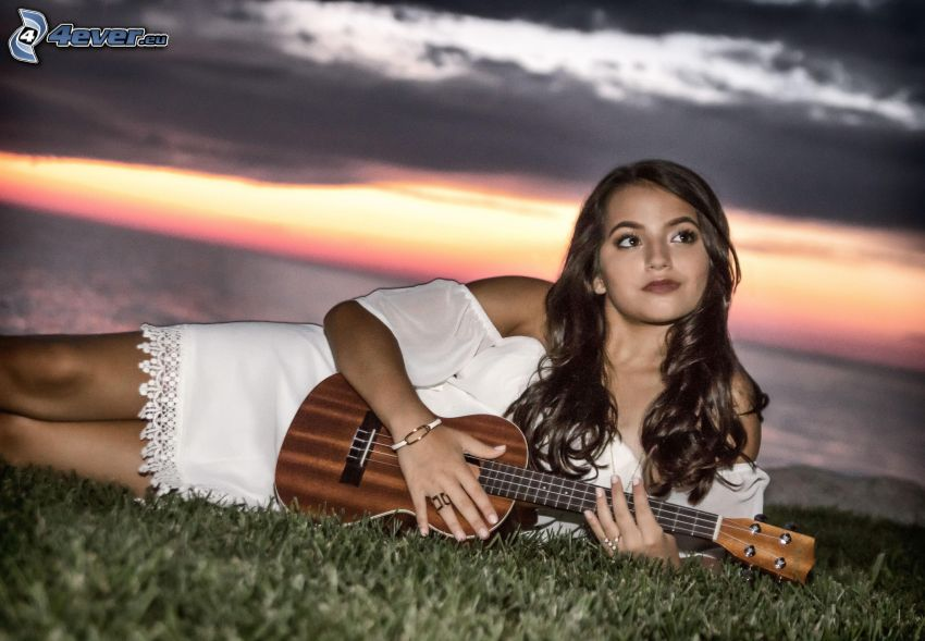 Isabela Moner, gra na mandolinie, ciemne chmury, biała sukienka