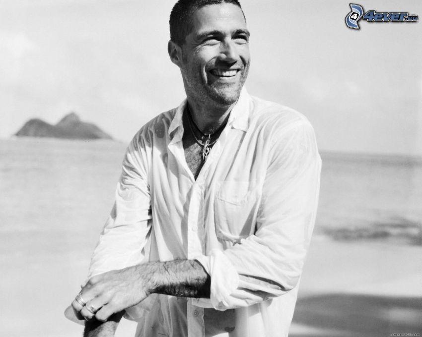Matthew Fox, uśmiech, plaża, biała koszula, czarno-białe zdjęcie