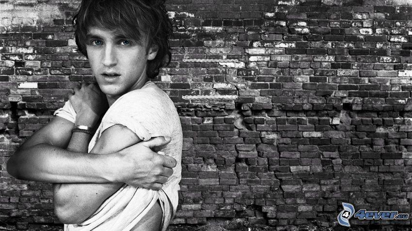 Tom Felton, ceglany mur, czarno-białe zdjęcie