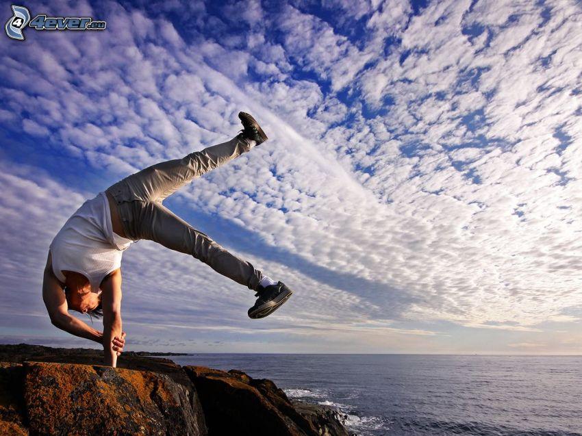 chłopak, akrobacje, skała, widok na morze, chmury