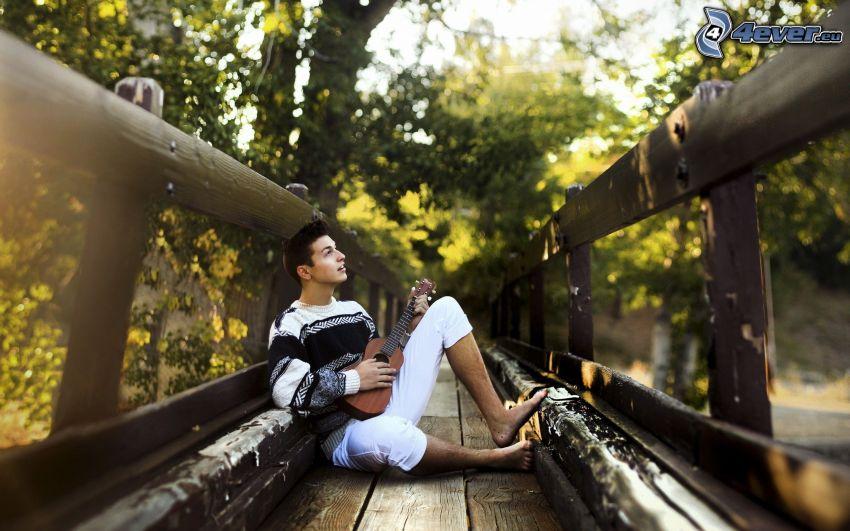 mężczyzna z gitarą, drewniany most
