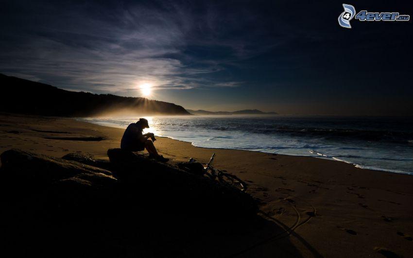 facet na plaży, ciemny zachód słońca, plaża piaszczysta, morze, plaża o zachodzie słońca