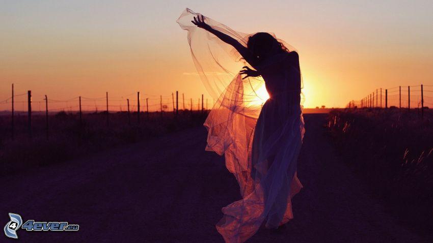 sylwetka kobiety, przy zachodzie słońca, ogrodzenie z drutu