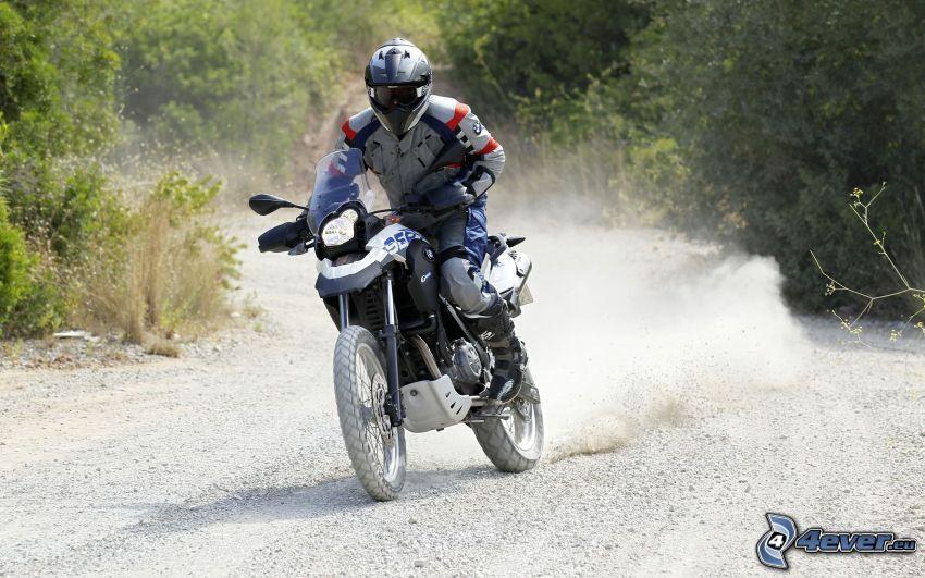 Motocykl BMW, motocyklista, pył, krzewy