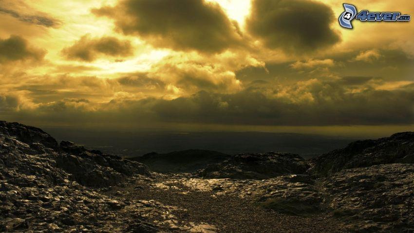 góry skaliste, żółte niebo, ciemne chmury
