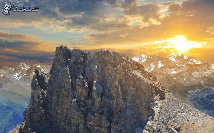 góry skaliste, słońce za chmurami, zaśnieżone góry