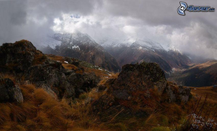 góry skaliste, zaśnieżone góry, chmury, sucha trawa