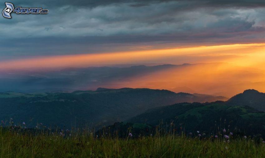wzgórza, pomarańczowy zachód słońca, chmury, łąka