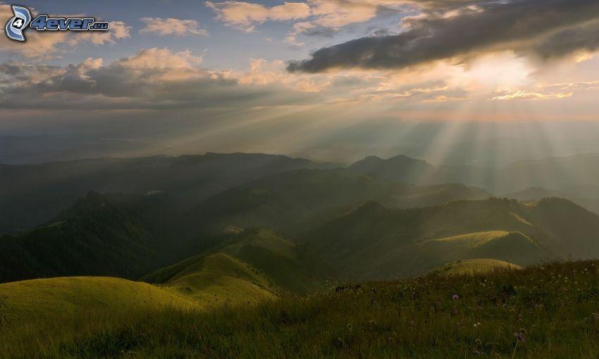 wzgórza, zieleń, promienie słoneczne, słońce za chmurami