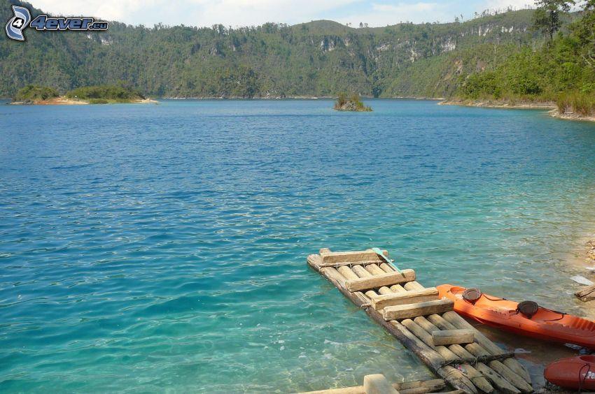 jezioro w lesie, tratwa, niebieska woda, skaliste wzgórza, drzewa