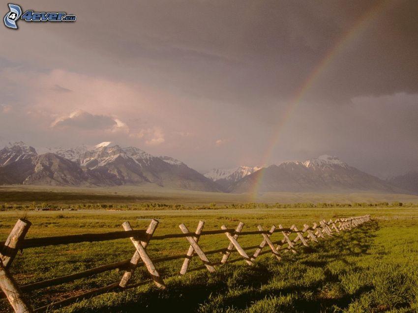 łąka, drewniany płot, tęcza, zaśnieżone góry