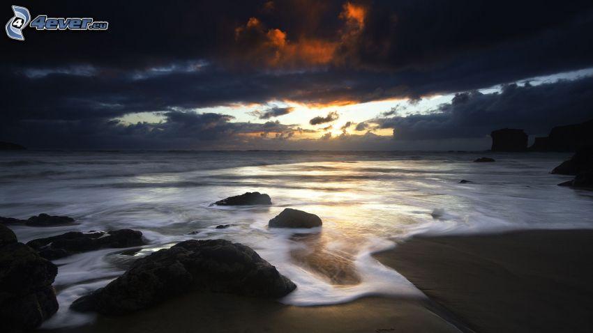 ciemne chmury nad plażą, morze, słońce, skały